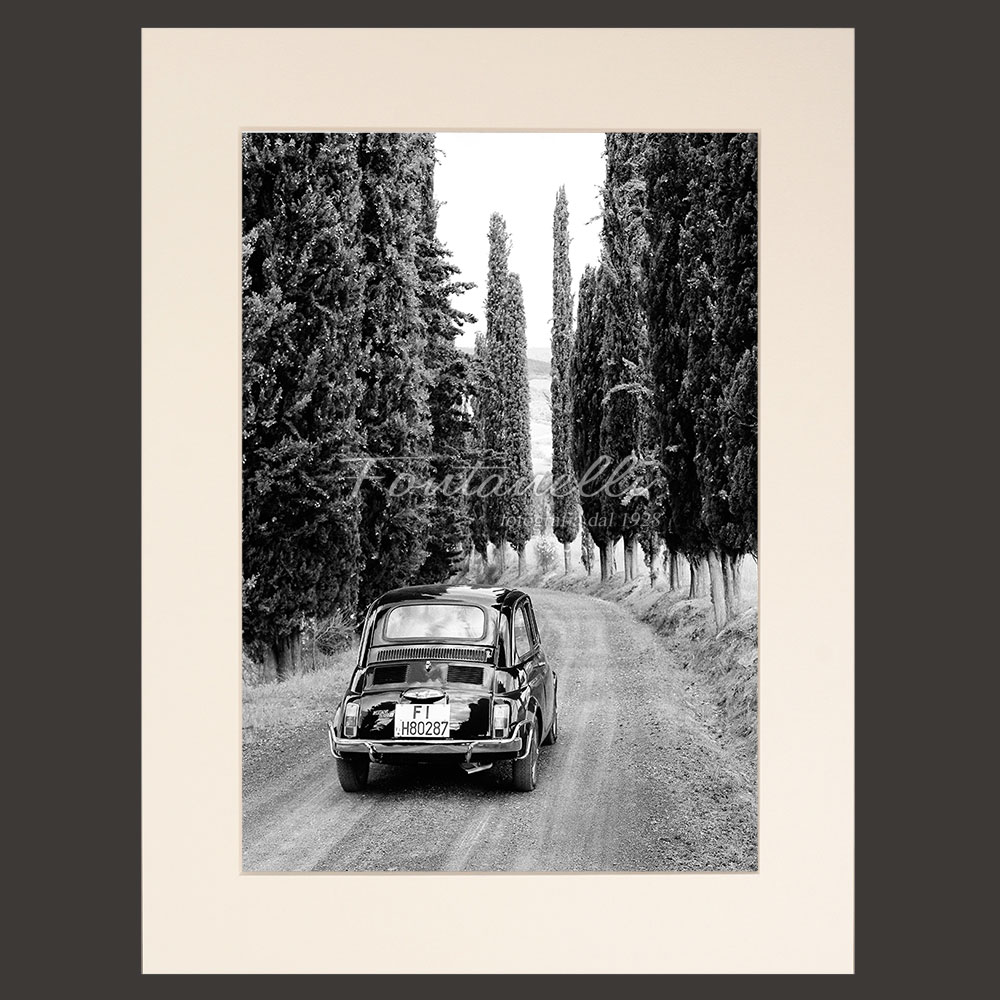 Fiat 500 on a typical street with cypress trees in Tuscany