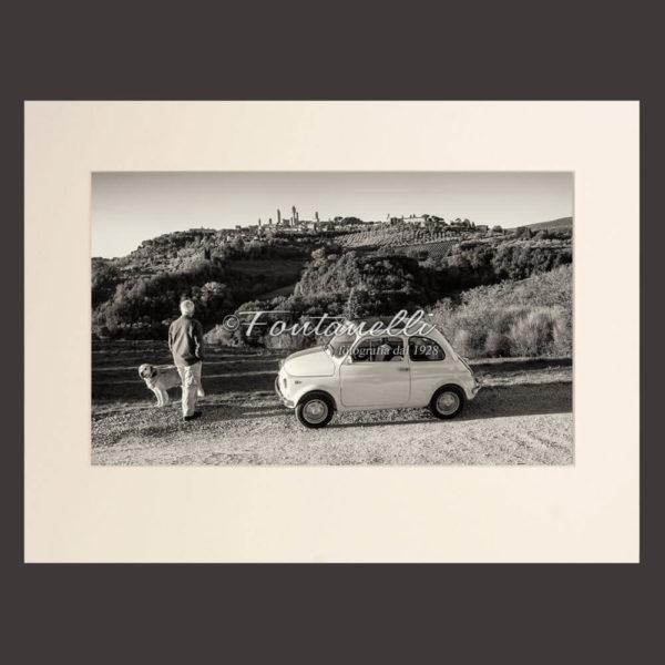 Foto bianco e nero Fiat 500 con paesaggio di San Gimignano sullo sfondo Toscana