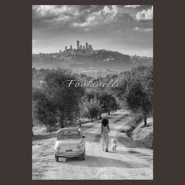 Foto di Fiat 500 con donna e cane sullo sfondo Di San Gimignano